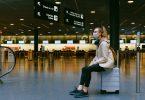 Femme assise sur son bagage à l'aéroport